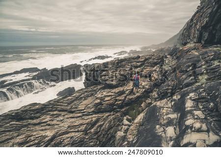 Female tourist hiking along the wild coast of Tsitsikamma National Park. Eastern Cape. South Africa. - stock photo