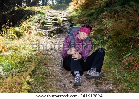 Female tourist injured an leg in mountains during the journey and trip - stock photo