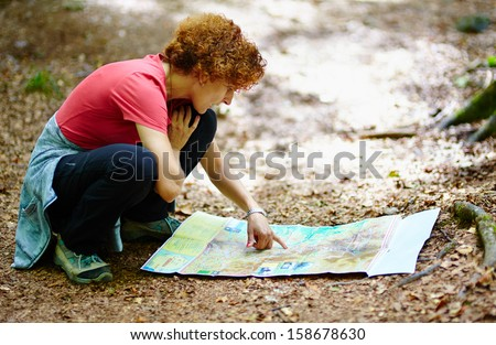 Female tourist looking on a map in a forest - stock photo