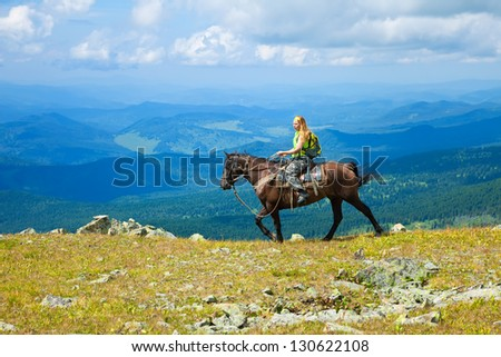 Female tourist on horseback at mountains.   Altai, Siberia - stock photo