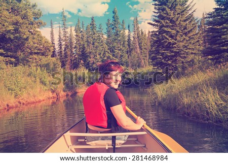 Female tourist paddling a canoe on the mountain  lake. Vermillion Lakes. Banff National Park, Alberta, Canada). Image done in vintage retro instagram style  - stock photo