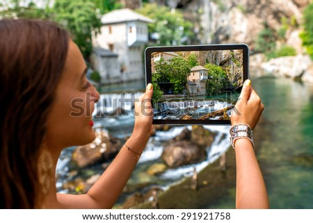 Female tourist photographing with digital tablet house on Buna spring in Blagaj village in Bosnia and Herzegovina