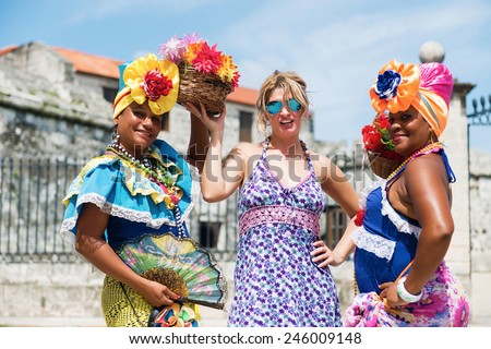 Female tourist posing between Cuban women on the Havana Cuba street,Shallow doff, best focus at the middle woman - stock photo