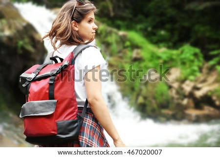 Female tourist standing beside the mountain river