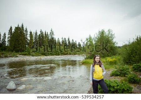 Female tourist standing beside the mountain river.