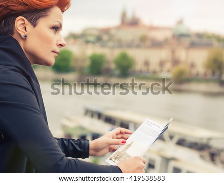 Female tourist standing near river and looking at city guide