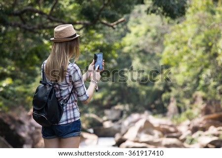 Female tourist taking picture with mobile phone for Instagram and other social media, forest and rocky river on the background - stock photo