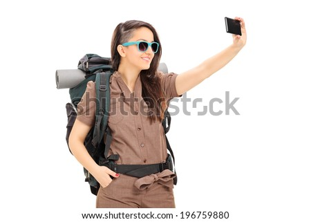 Female tourist taking selfie with cell phone isolated on white background - stock photo