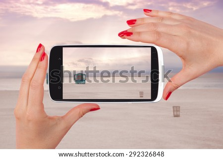 Female tourist taking snapshot with smartphone of lifeguard cabin, Miami Beach, Florida, USA. Backpacking, vagabonding, travelling. - stock photo