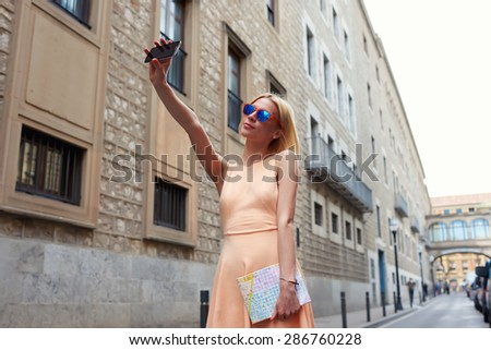 Female tourist using mobile phone camera for take a picture of herself during vacation holidays in Barcelona, stylish young woman taking self portrait with smart phone,feeling good and happy in travel - stock photo