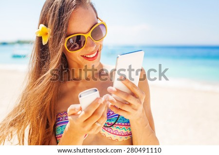 female tourist using portable power bank to charge her phone on a beach - stock photo