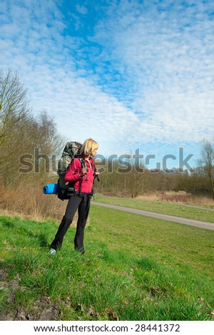 Female tourist with a big backpack on grass. - stock photo
