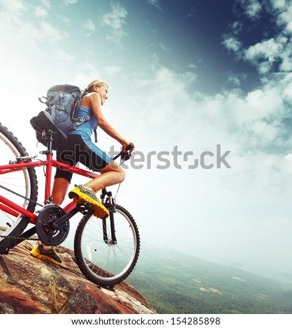 Female tourist with backpack and bicycle enjoying valley view from top of a mountain - stock photo