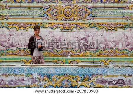 Female tourist with camera in her hand as a part of a very colorful composition of tiles outside the Queluz National Palace of Sintra, Portugal - stock photo