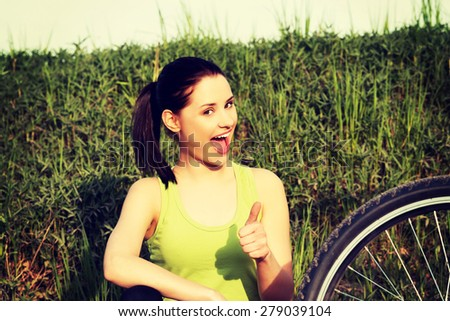 Female tourist with mountine bicycle gesturing ok - stock photo