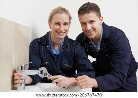 Female Trainee Plumber Working On Tap In Bathroom - stock photo