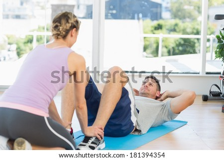 Female trainer assisting fit man in doing sits up at gym - stock photo