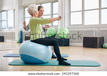 Female trainer assisting senior woman lifting weights in gym. Senior woman sitting on pilates ball doing weight exercise being assisted by personal trainer at health club. - stock photo