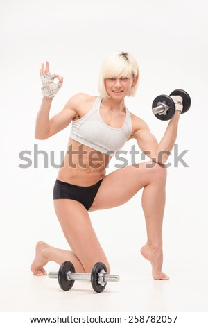 female trainer demonstrates the muscles in her arms , and holding dumbbells. isolated on white background