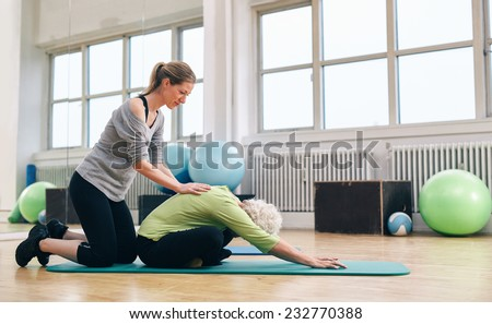 Female trainer helping senior woman to bend over. Old woman doing yoga on a exercise mat with physical therapist helping at gym.