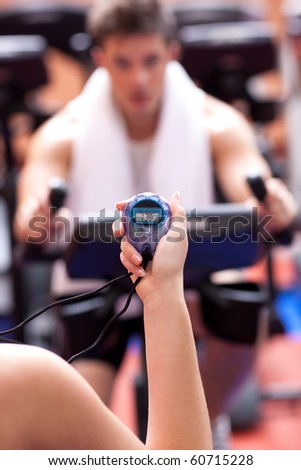 female trainer holding a chronometer while man doing physical execice on a bicycle - stock photo