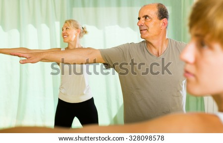 Female trainer showing positive senior couple how to incline the body