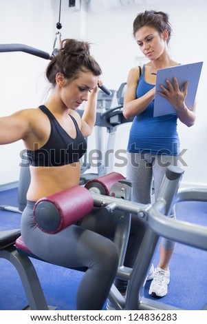 Female trainer taking notes on client on weights machine in gym