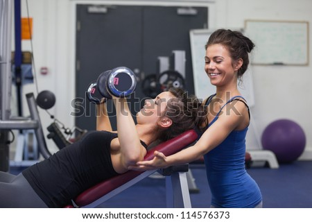 Female trainer teaching woman lifting weights in gym