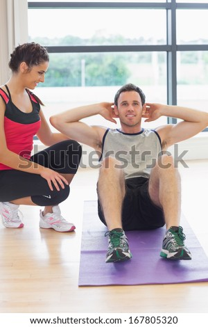 Female trainer watching young man do abdominal crunches on exercise mat at a bright gym - stock photo