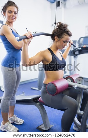 Female trainer with client on weights machine in gym