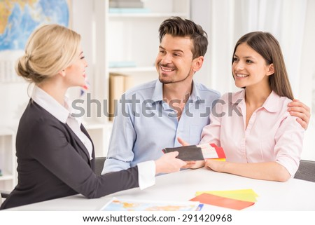 Female travel agent giving tickets to young happy couple. - stock photo