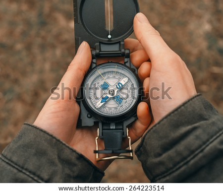 Female traveler holding a compass on nature. Point of view shot. Close-up image - stock photo