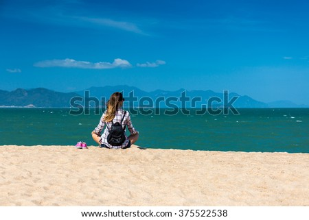 Female traveler on seashore relaxing with island view