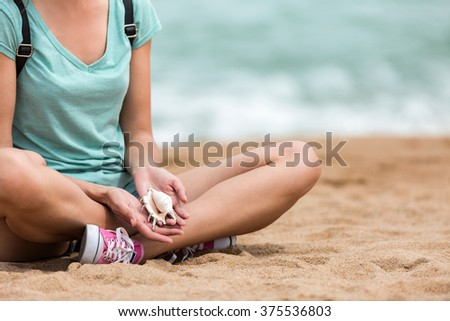 Female traveler relaxing on seashore, holding conch seashell