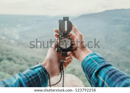 Female traveler searching direction with a compass in the mountains. Point of view shot