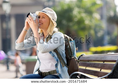 female traveler taking photo with digital camera in the city - stock photo