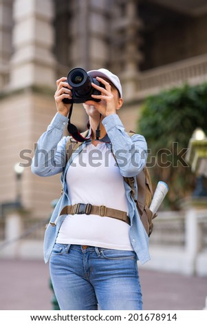 female traveler taking photos using digital camera in the city  - stock photo