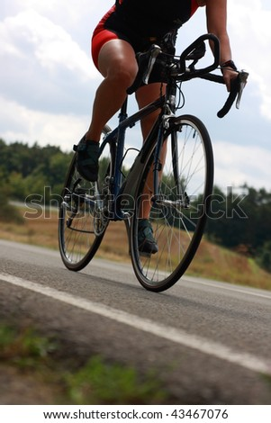 female triathlete on bicycle with slight motion blur - stock photo
