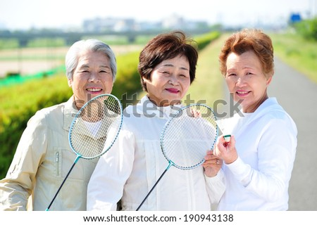 Female trio that pose happily with a racket - stock photo