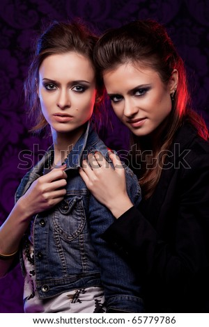 Female twins in colored light, studio shooting, low key.