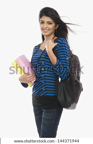 Female university student holding books and smiling - stock photo