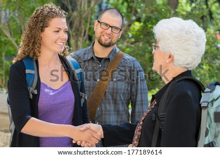 Female university students shaking hands at university campus with professor - stock photo