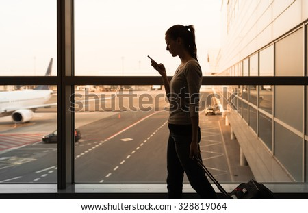 Female using her phone while walking in the airport. - stock photo