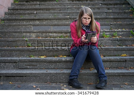 Female using tablet sitting on steps outdoors - stock photo
