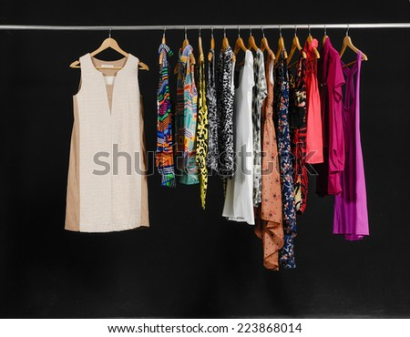 Female Variety of clothes hanging on the rack-black background - stock photo