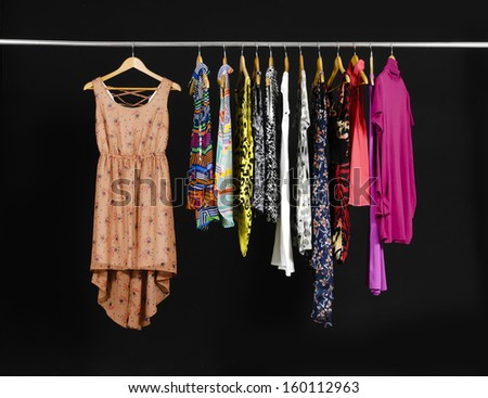Female Variety of colorful clothes hanging on black background