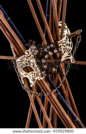 Female Venice mask brooch on wooden sticks on black background - stock photo