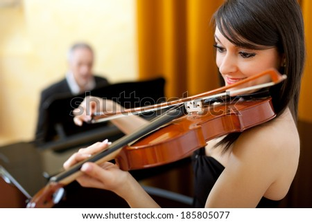 Female violinist and male pianist playing together