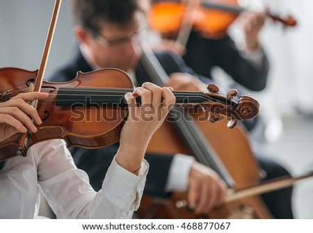 Female violinist performing and classical orchestra on background, selective focus, music and arts concept