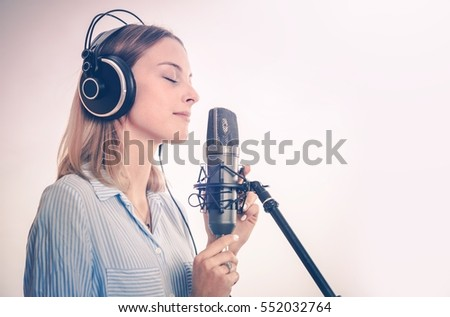 Female Vocal Recording. Young Woman with Microphone and Headphones in the Recording Studio.